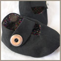 Black baby booties with snap closure